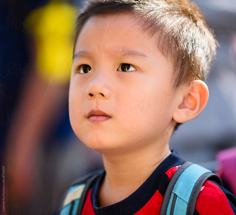 Child looking up with serious face by Lawren Lu for Stocksy United