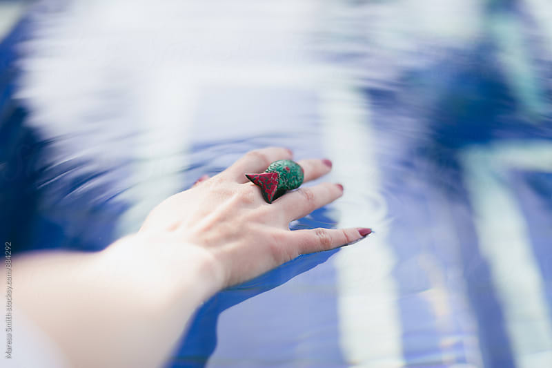A female hand touching the water at a blue swimming pool by Maresa Smith for Stocksy United
