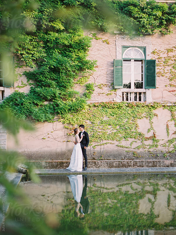 Bride and groom kissing at pond