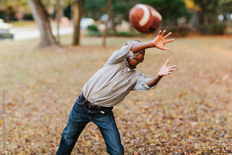 A young boy in the neighborhood park playing catch with a football by Kristen Curette Hines for Stocksy United