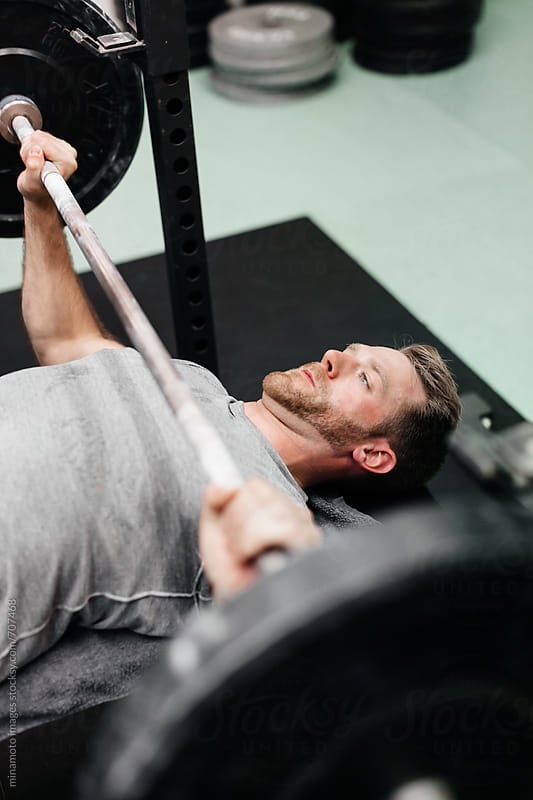 Athlete Doing Bench Press by minamoto images for Stocksy United
