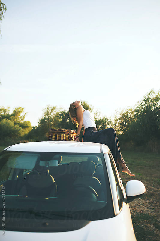 Beautiful young woman sitting on a car  by Jovana Rikalo for Stocksy United