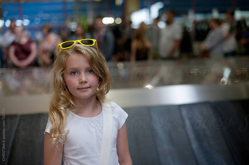 Girl waiting for luggage at the airport by CHRISTINA K for Stocksy United