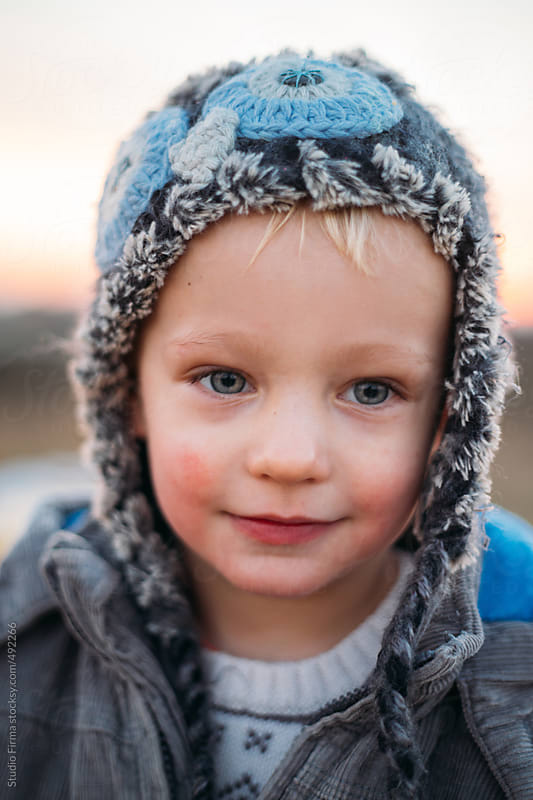 Potrait of a young blonde little boy with funny winter cap. by Studio Firma for Stocksy United