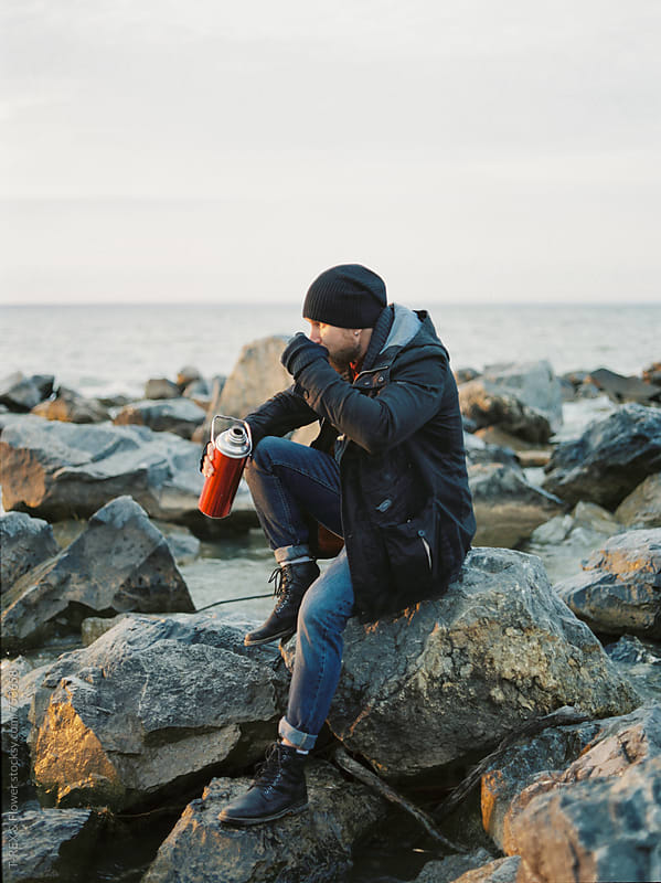 Man drinking tea from thermos by Danil Nevsky for Stocksy United