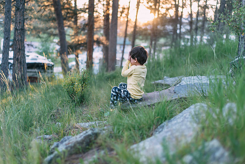 little boy covers his eyes to play hide and seek in a campground by Tara Romasanta for Stocksy United