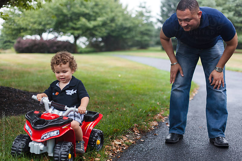 A father watches his son ride a motorized toy car. by Holly Clark for Stocksy United