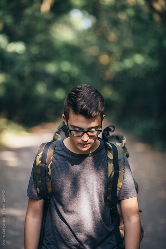 Teenager outdoors; Young teen boy with a backpack exploring the forest by Adrian Cotiga for Stocksy United