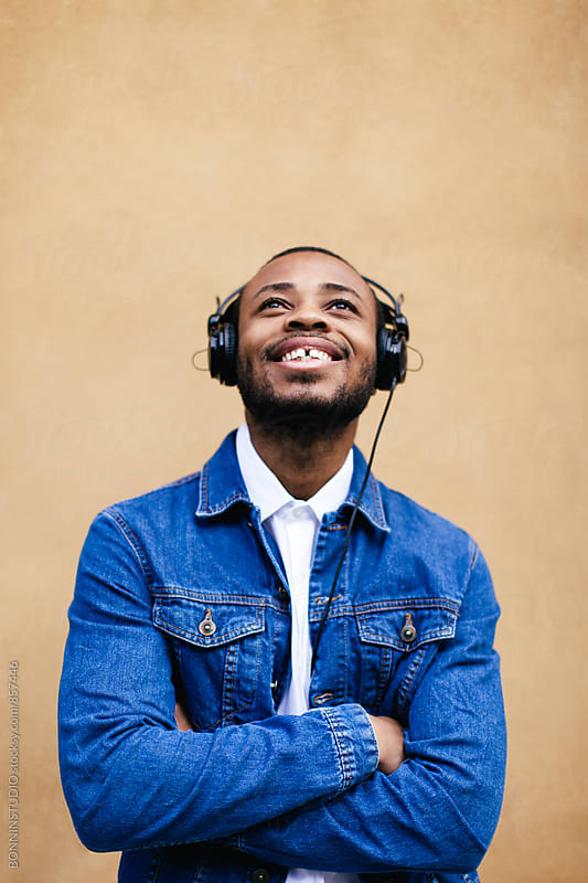 Portrait of a happy man listening music with headphone. by BONNINSTUDIO for Stocksy United