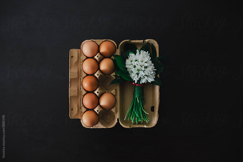 Eggs and a boqueut of snowdrops on a table by Marija Mandic for Stocksy United