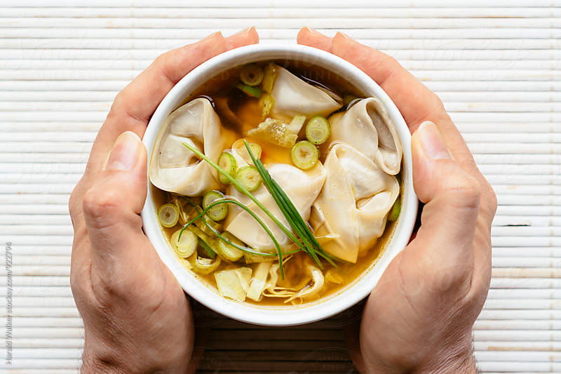 Hands holding a shiiatke wonton soup by Harald Walker for Stocksy United