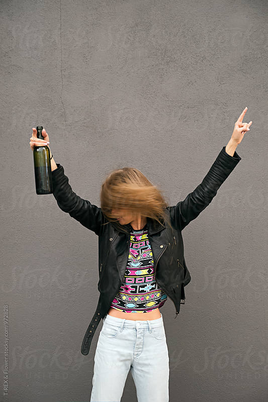 Young woman with drink and arms up on grey background by Danil Nevsky for Stocksy United