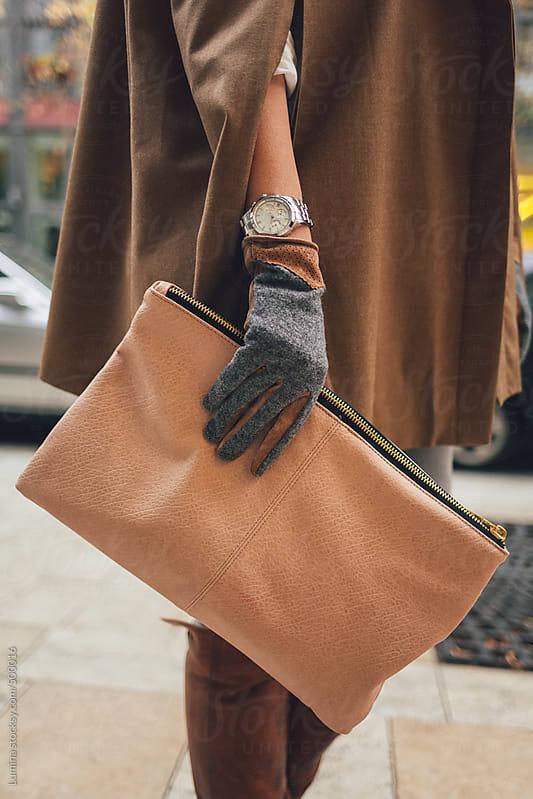 Elegant Woman Holding a Handbag by Lumina for Stocksy United
