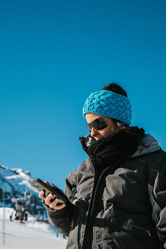 Woman Using Her Mobile Phone in a Snowy Scenery by VICTOR TORRES for Stocksy United