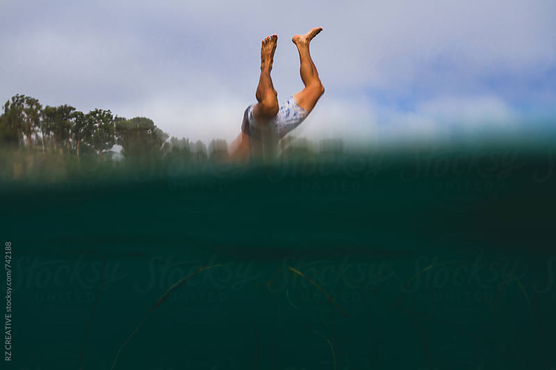 Person leaping head-first into the ocean. by Robert Zaleski for Stocksy United