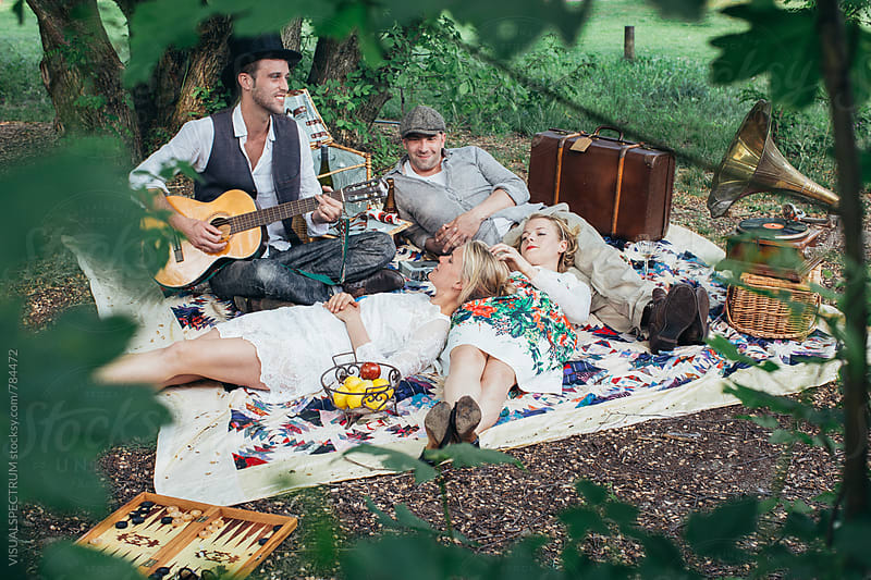 Retro Picnic - Four Friends Enjoying Themselves on a Spring Day in Green Countryside by Julien L. Balmer for Stocksy United