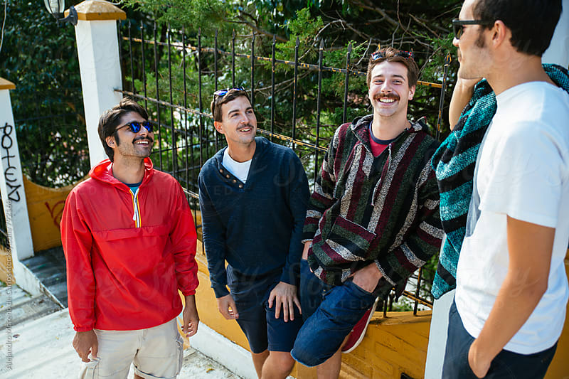 Four young smiley men having a conversation standing on the steps of some stairs by Alejandro Moreno de Carlos for Stocksy United