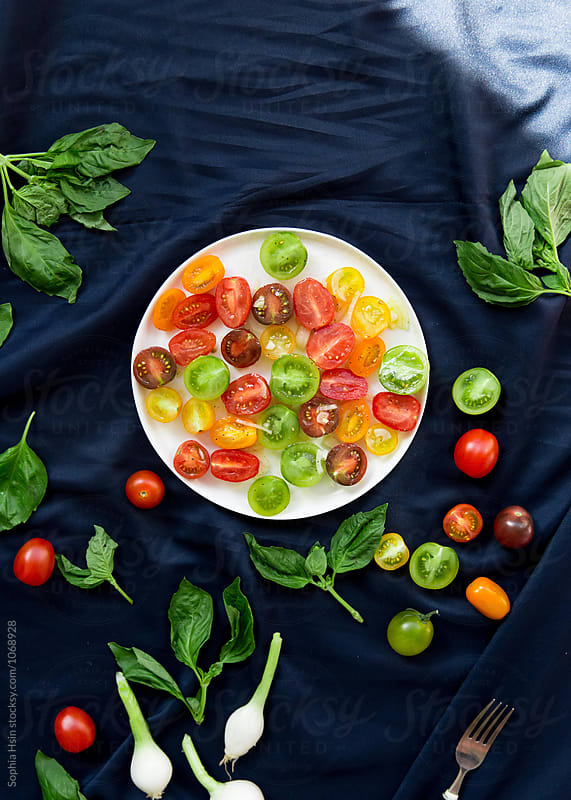 Colorful tomato's with vegetables on dark background by Sophia Hsin for Stocksy United