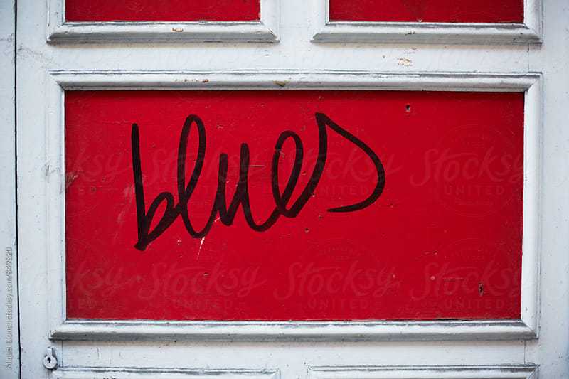 Blues word on a red door by Miquel Llonch for Stocksy United