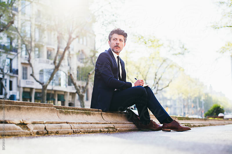 Mature businessman sitting on the street. by BONNINSTUDIO for Stocksy United