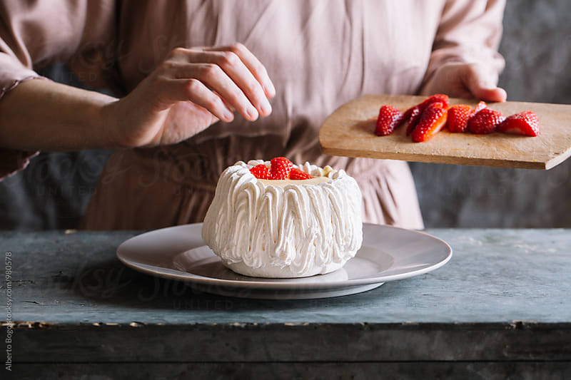 Woman decorating pavlova cake with strawberry by Alberto Bogo for Stocksy United