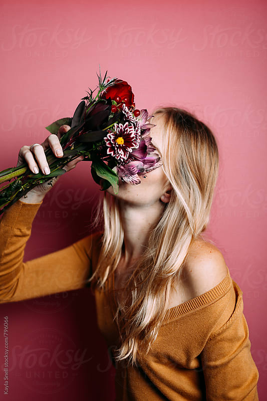 Woman with a bouquet of flowers by Kayla Snell for Stocksy United