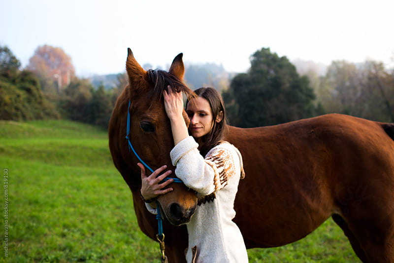Woman embraces with affection her horse by michela ravasio for Stocksy United
