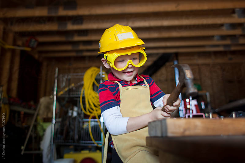 Little Boy in Garage Hammering a Nail with Hardhat and Goggles by JP Danko for Stocksy United