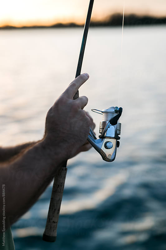 Hands on fishing for and reel waiting patiently for bite by Matthew Spaulding for Stocksy United