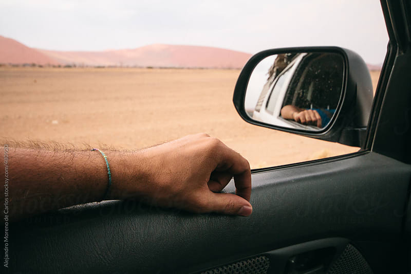 Hand detail of a man traveling on a car through the desert on adventure travel by Alejandro Moreno de Carlos for Stocksy United
