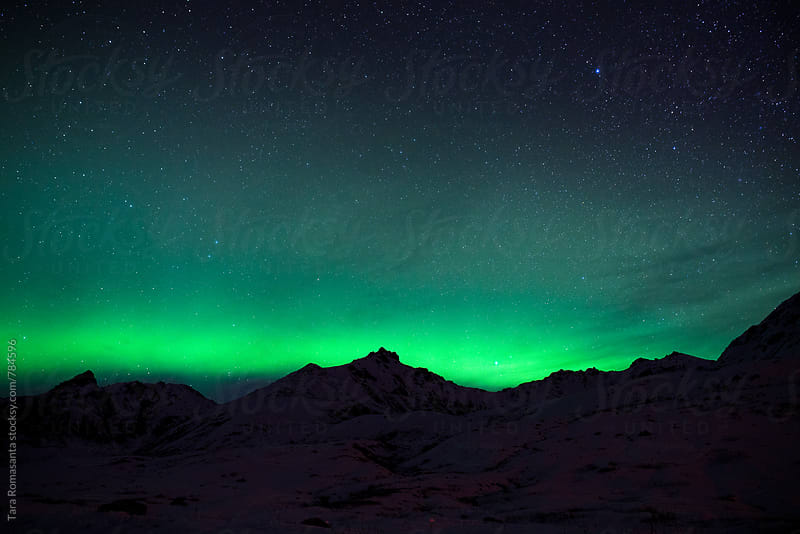 low aurora borealis band over a mountain ridge  by Tara Romasanta for Stocksy United