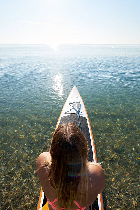 Overhead of woman sitting on paddle surf against of endless sea by Guille Faingold for Stocksy United