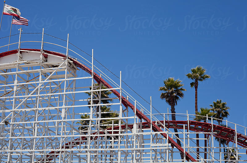 Roller coaster with palm trees against a blue sky by Carolyn Lagattuta for Stocksy United