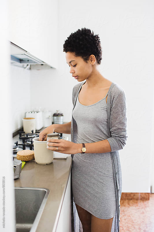 African girl preparing coffee in the kitchen by michela ravasio for Stocksy United