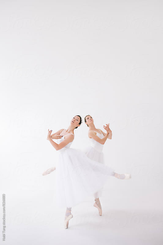 Two beautiful ballerinas in white costume dancing together by Nabi Tang for Stocksy United