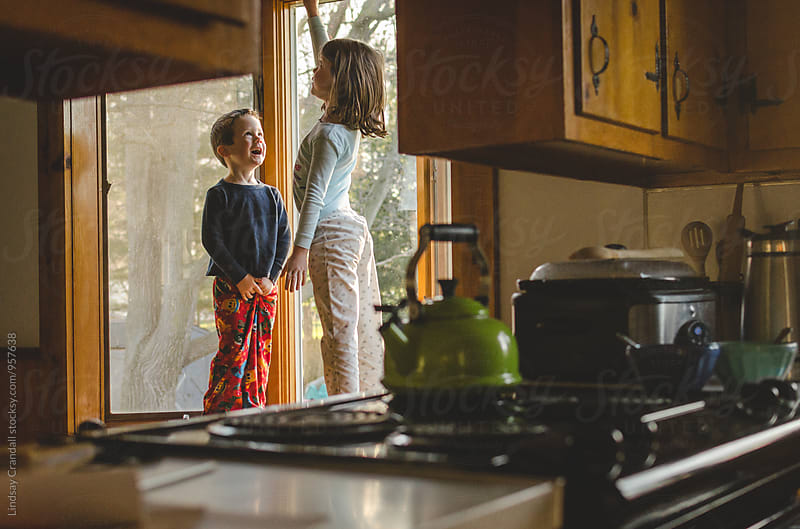 Two children standing in the windowsill on the far side of a kitchen by Lindsay Crandall for Stocksy United