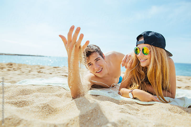 Teenage couple playing with the sand on the beach. by BONNINSTUDIO for Stocksy United