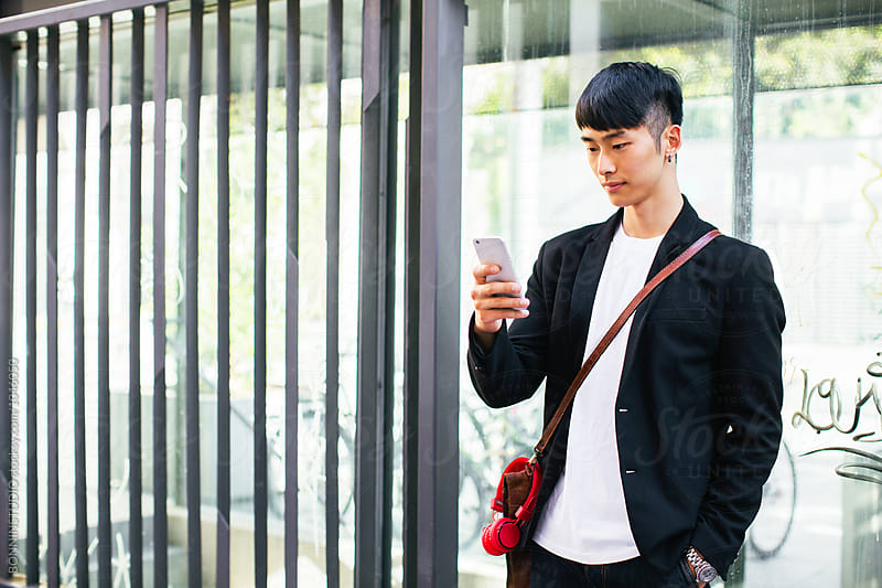 Asian businessman using his phone on the street. by BONNINSTUDIO for Stocksy United