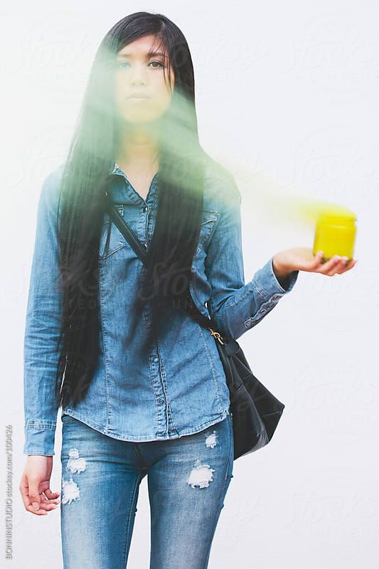 Asian woman with yellow smoke bomb. by BONNINSTUDIO for Stocksy United