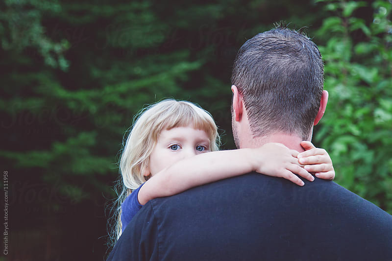 A father holds his little daughter as she peeks over his shoulder. by Cherish Bryck for Stocksy United