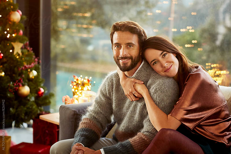 Happy Woman Embracing Man On Sofa During Christmas by ALTO IMAGES for Stocksy United