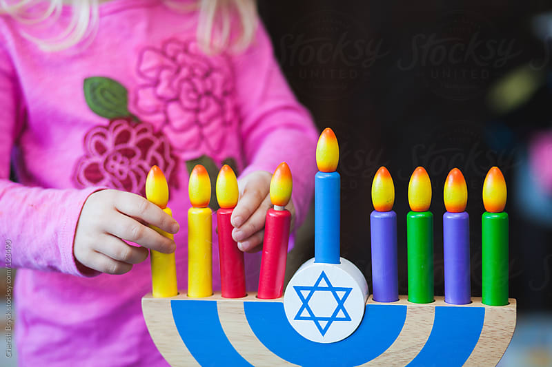 Child playing with toy Menorah. by Cherish Bryck for Stocksy United