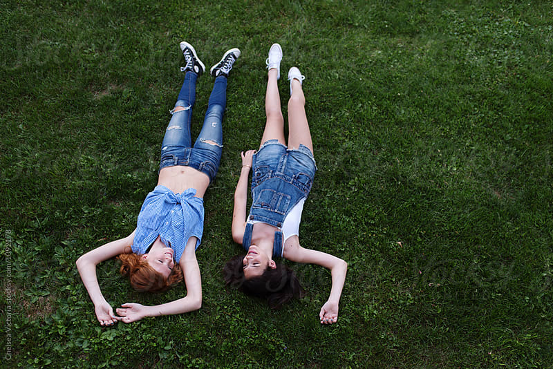 Two best friends laying in the grass taking pictures with their phone by Chelsea Victoria for Stocksy United
