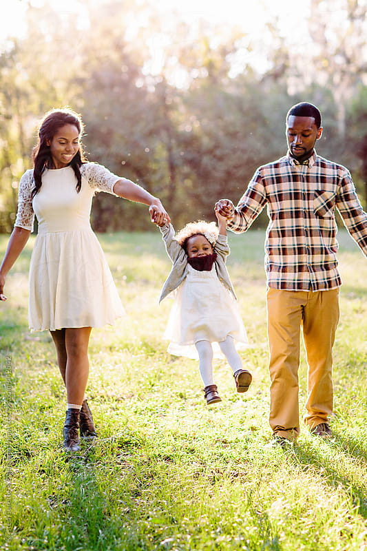 A Beautiful African American Family Playing With Their Little Girl In The Park By -9257