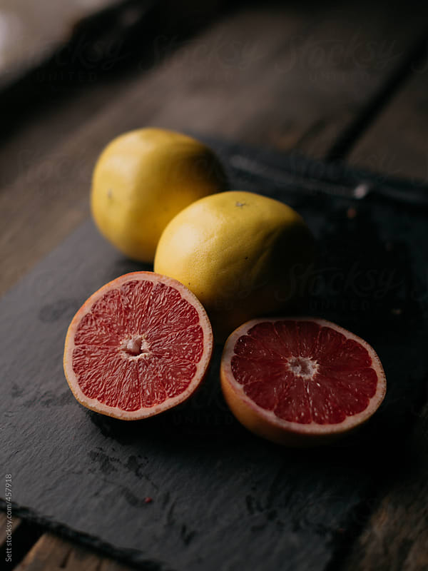 Freshly cut grapefruit in beautiful wooden kitchen by Levi Tijerina for Stocksy United