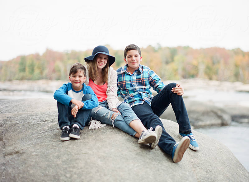 Three siblings smiling and sitting on a river rock by Marta Locklear for Stocksy United