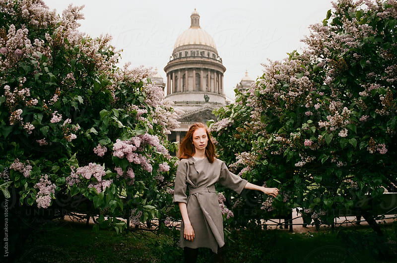 Woman standing in front lilac shrubs and looking at camera by Lyuba Burakova for Stocksy United