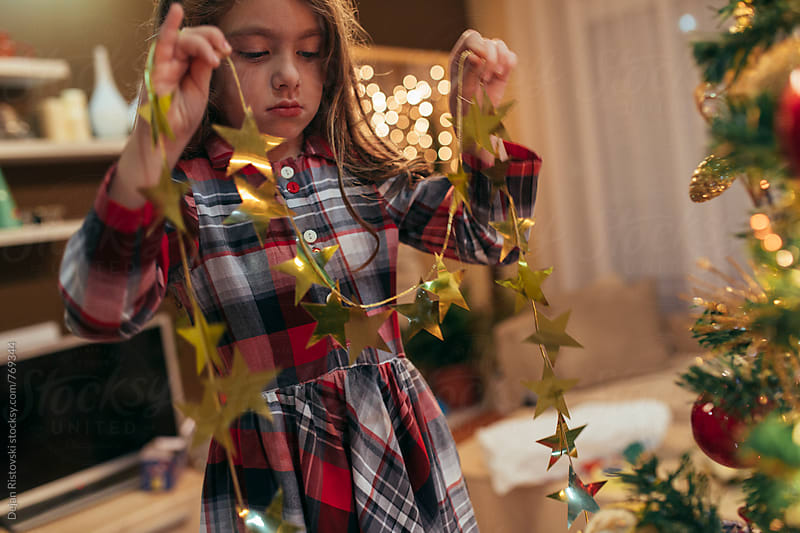 Cute girl decorating Christmas tree by Dejan Ristovski for Stocksy United