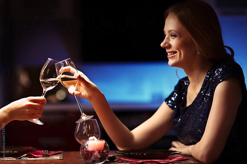 Young woman toasting with friend in restaurant by Ilya for Stocksy United
