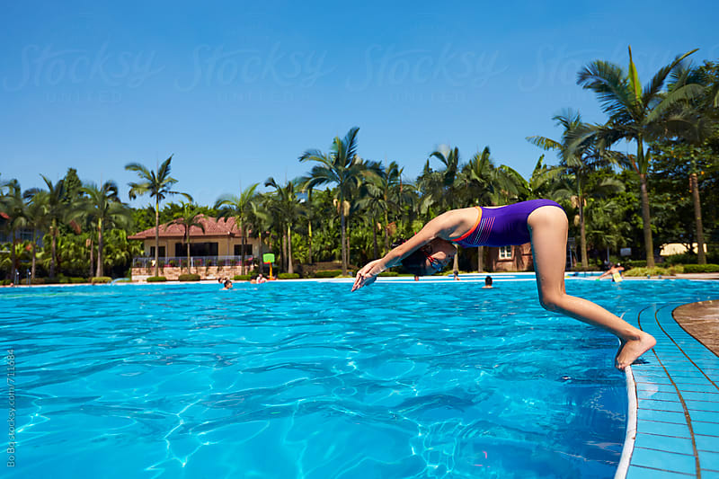 little asian girl jumping into the swimming pool by cuiyan Liu for Stocksy United